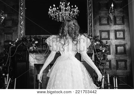 Woman with long curly hair in a white vintage wedding dress. Black and white art monochrome photography. Black and white creative photography. Black and white conceptual image. Beautiful black and white background.