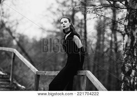 Striking girl with long hair in black clothes. Black and white art monochrome photography. Black and white creative photography. Black and white conceptual image. Beautiful black and white background. Black and white portrait.