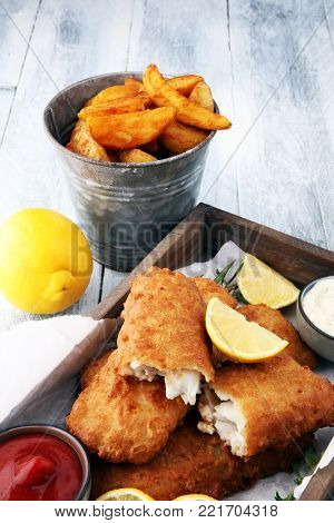 traditional British fish and chips with potato and lemon