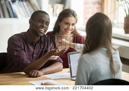 Happy multiracial couple getting keys to new home from realtor, excited young customers buying real estate house concept, diverse family buyers purchasing property, mortgage loan investment deal