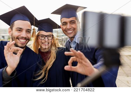 education, graduation, technology and people concept - group of happy international students in mortar boards and bachelor gowns taking selfie by smartphone outdoors and showing ok hand sign