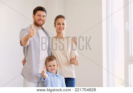 mortgage, people and real estate concept - happy family with child moving to new home and showing thumbs up