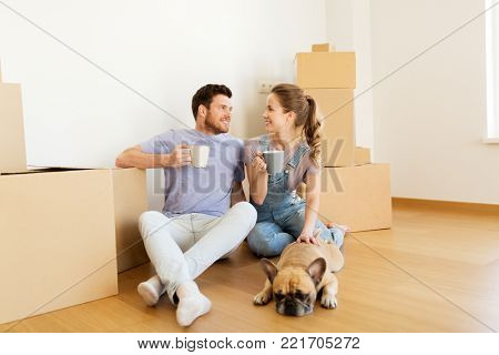 mortgage, people and real estate concept - happy couple with boxes and french bulldog dog moving to new home and drinking coffee