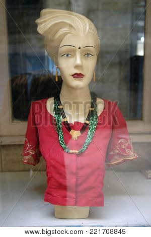 Mannequin, the upper half of a woman in a red jacket and stone beads in a shop window.