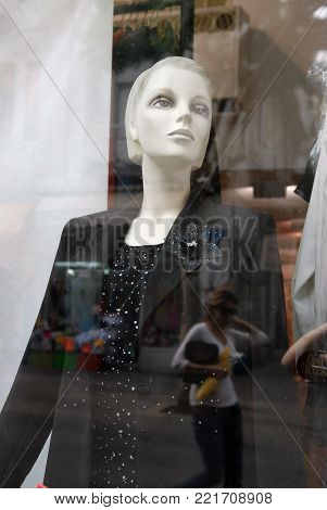 Mannequin woman in black clothes through a glass in the surface of which the walking men are reflected.