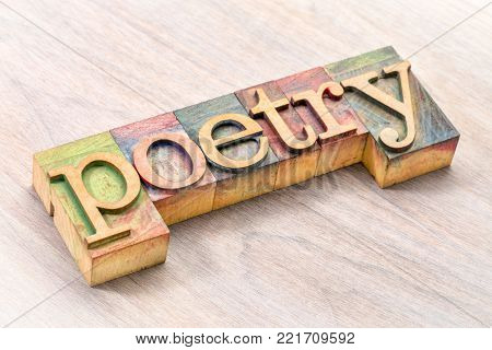 poetry word abstract- text in vintage  letterpress wood type blocks against grained wood