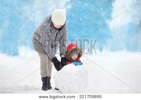 Little boy with his mother/babysitter/grandmother building snowman in snowy park. Active outdoors leisure with children in winter. Kid during stroll in a snowy winter park