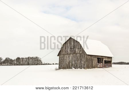 Brown barn with a snow-covered roof in a snow-covered field