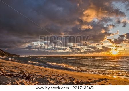 Dark clouds contrasting with a bright setting sun on a deserted beach on Lake Michigan