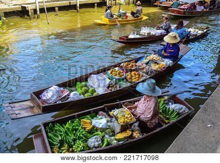 Bangkok, Thailand - Jun 19, 2017. Vendors selling food on boat at Damnoen Saduak Floating Market in Bangkok, Thailand. Damnoen Saduak is Thailand most popular floating market.