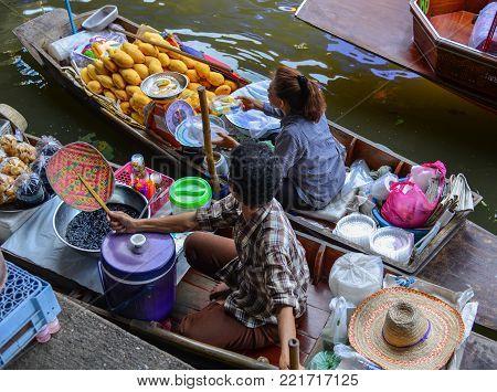 Bangkok, Thailand - Jun 19, 2017. People selling food on boat at Damnoen Saduak Floating Market in Bangkok, Thailand. Damnoen Saduak is Thailand most popular floating market.