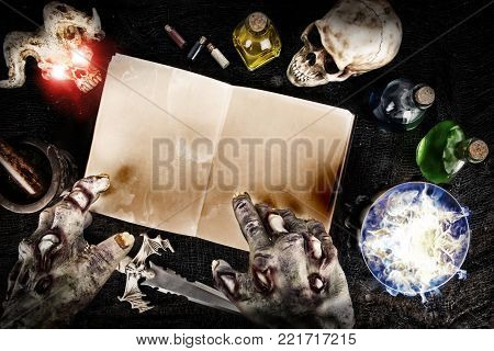 Halloween composition with mysterious bottles and black magic book. Top view.
