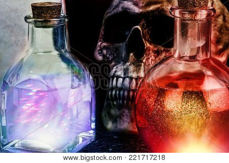 Halloween composition with mysterious bottles of magic potion and skull in the background. Close up.