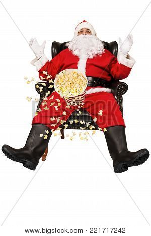 Surprised Santa Claus sits in chair and popcorn flying in the air, isolated on white background.