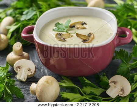 Cream soup of mushrooms with croutons in a purple bowl on a dark wooden table. Cream soup of mushrooms, potatoes and cream with spices. The decoration of raw mushrooms.