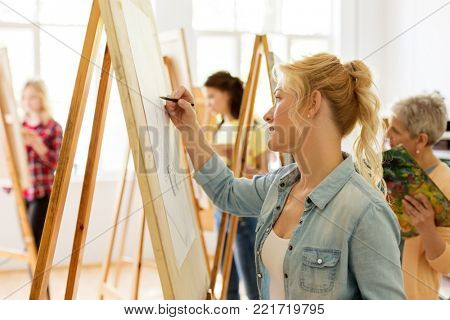 art school, creativity and people concept - woman with easel drawing at studio