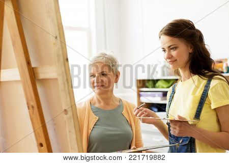 creativity, education and people concept - female artists or student girl with brush and palette and teacher painting on easel at art school studio
