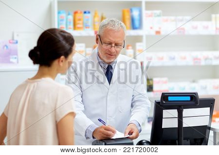 medicine, healthcare and people concept - senior apothecary writing precription for female customer at pharmacy