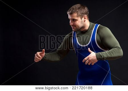 A young dark-haired man fighting Greco-roman wrestling and grappling in a blue   tights  , training mask  posing against a black isolated  background poster