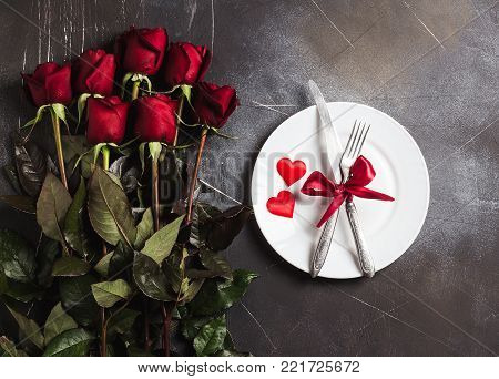 Valentines day table setting romantic dinner marry me wedding engagement with red rose gift and plate fork knife on dark background with copyspace. Love flower gift woman making proposal