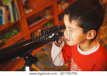 a boy looks through a telescope. inquisitive child exploring the world. astronomy for kids.