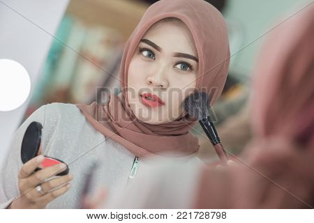 Beauty muslim woman with hijab applying makeup. Beautiful girl looking in the mirror and applying cosmetic. Girl gets blush on the cheekbones