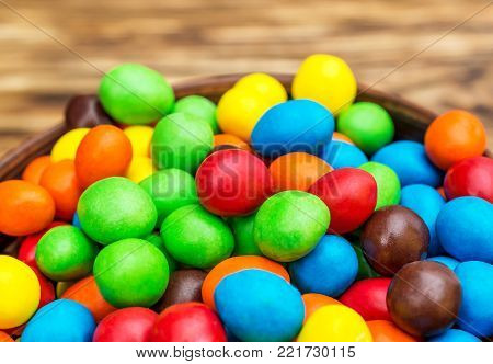 Macrophotography of bowl with round colorful candies on the table.