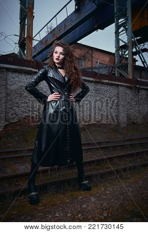 Fashion shot: portrait of a beautiful goth girl (informal model) in leather coat standing at railroad (industrial area)