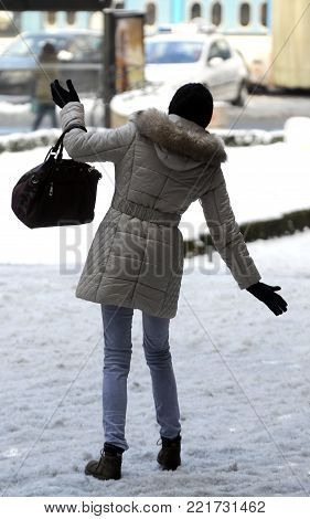 Young woman walking on slippery floor on snow