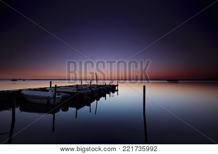 Motorboats docked at a jetty in a quiet lake under a colourful sky at dawn