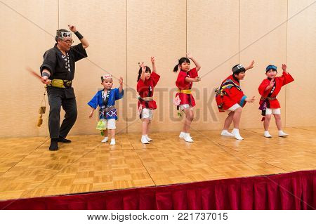 Hokkaido, Japan - 28 December 2017 - Japanese local performers, kids and adult, in traditional Japanese dress perform traditional local Japanese style dance for hotel guests at Eclipse hotel in Hokkaido, Japan on December 28, 2017