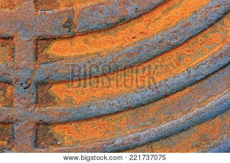 Fragment of an old rusty sewer hatch. Manhole cover closeup. Background or texture.