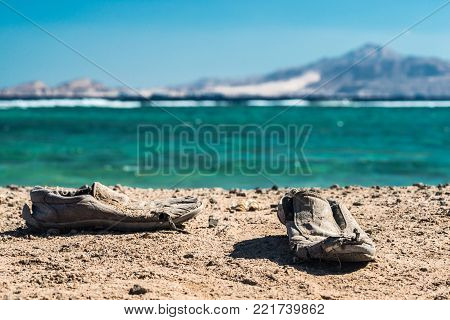 Pair of old shabby shoes on the sandy beach. Old shabby shoes on the sand