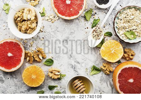 Ingredients of healthy breakfast food: oat flakes, kinoa, walnuts, floral honey, greens, oranges, bloody grapefruits on a light marble background. Top View