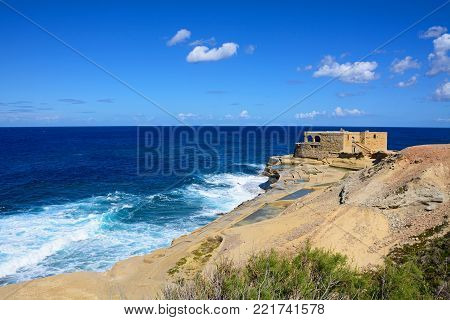 Salt pans along the waterfront with the Il-Qolla I-Badja battery to the rear, Redoubt, Marsalforn, Gozo, Malta, Europe.