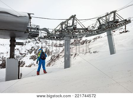 Young woman snowboarder in motion on snowboard in mountains along the cable ropeway in mountains Caucasus