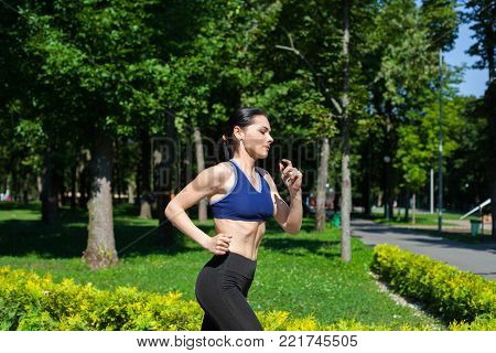 Young sportive teenager in a bright blue sport bra and black leggings running along the path in park. Photo of an athlete girl with a beautiful sports body