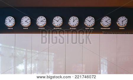 Clocks on wall showing time in Tokyo, Paris, London, Shanghai, Sydney, new York, Frankfurt Dubai