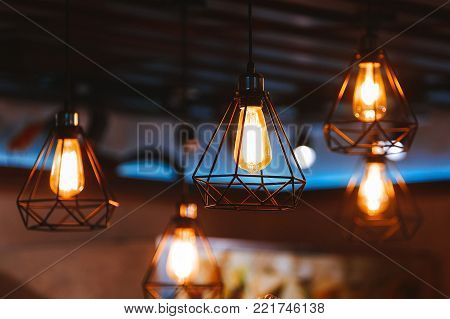 Lighting lamp is hanging at ceiling, spider web design lamp. Stylish lamp bulb in the interior