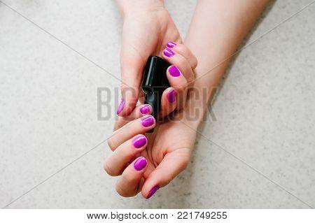 In the hands of gel nails, gel nail manicure primer base. Bank black. Nails purple, pink.