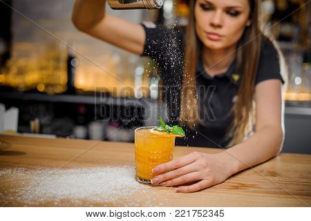 elegant barmaid finishes preparation of orange alcoholic cocktail decorated with a sprig of mint and a slice of dried orange in crystal glass by adding a bitter of powdered sugar.