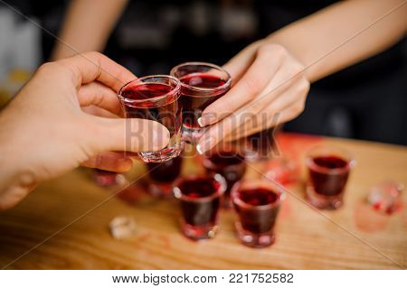 pretty barmaid clinks glasses with a red-colored alcohol on a bar counter with a guest