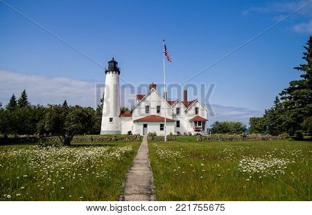 Scenic Michigan Lighthouse Landscape. Wildflowers frame a scenic lighthouse on the shore of Lake Superior. The Point Iroquois Lighthouse is a historical scenic site in the Hiawatha National Forest.
