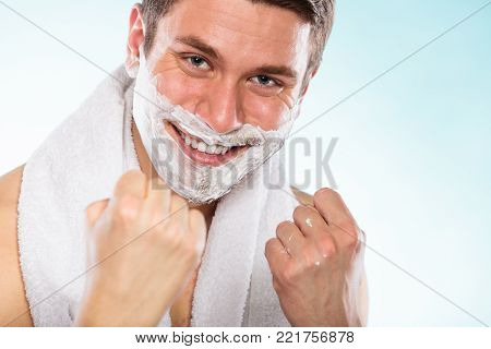 Happy young man with shaving cream foam and white towel having fun. Handsome guy preparing to shave. Skin care and hygiene.