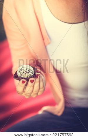 Food and sweets. Appetite and tasty meal dessert. Part body woman with little cookie cupcake. Hand holding small cake.