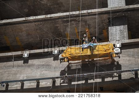 Hong Kong - July 13, 2017: Modern building is under construction, concrete floors. Chinese workers work on the cradle
