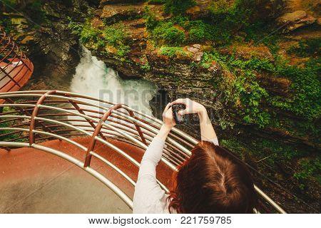 Tourist attraction in Norway, Europe. Woman photographer taking photo with camera on Gudbrandsjuvet viewpoint, Valldalen valley, between Valldal and Trollstigen.