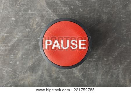 Overhead of a red pause push button on concrete background