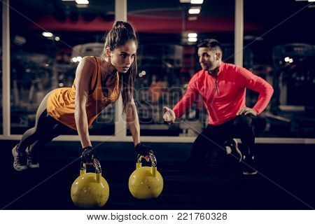 Close up of focused and motivated strong young fitness woman in sportswear doing push ups on the kettlebells while her personal trainer kneeling next to her and supporting.
