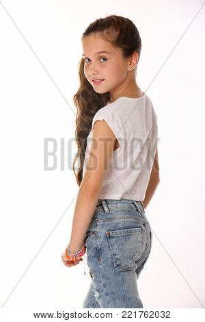Portrait of pretty beautiful brunette young teen girl in blue jeans. The adorable slender preteen posing on a white background. The image of children's summer fashion. poster